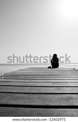 A girl resting in a quiet lake scenery - stock photo