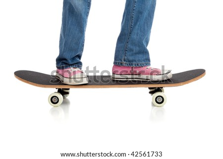 A girl's legs in jean and pink sneakers riding a skateboard on a white background