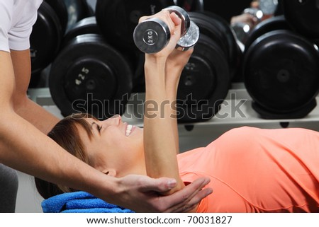 A girl's trainer shows her the correct form of exercise with dumbbell