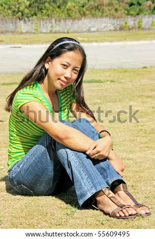 A girl seating in the grass