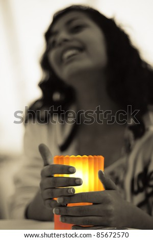 A girl seeking warmth from a lit candle. - stock photo