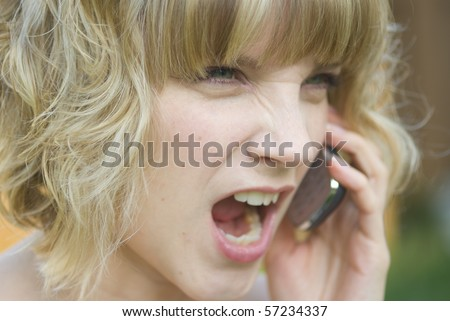 A girl shouting on a phone - stock photo