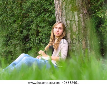 A girl sits near a tree, leaning on it. - stock photo