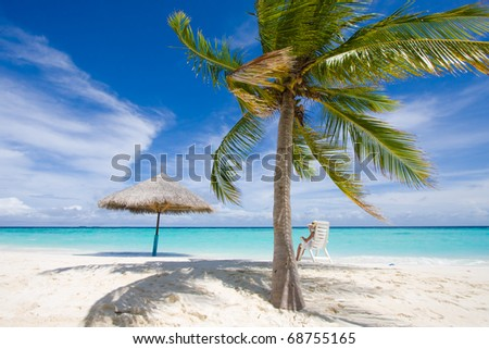A girl sits on a chair under a palm - stock photo