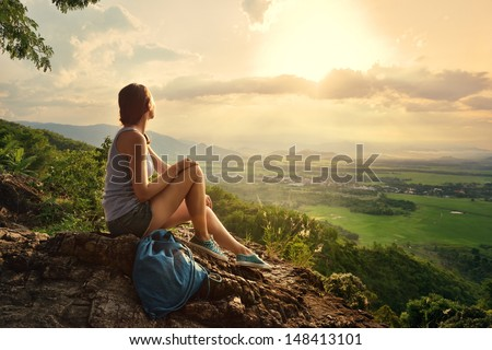 A girl sits on the edge of the cliff and looking at the sun valley and mountains - stock photo
