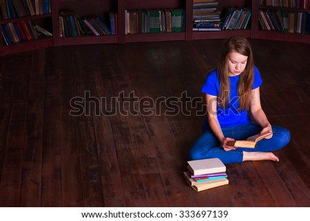 A girl sits on the floor in the library