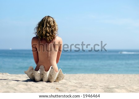 A girl sitting in sea shell on the beach - stock photo