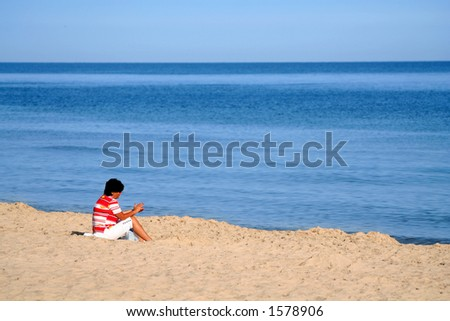 a girl sitting in the sand at the beach