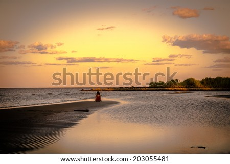 A girl sitting on a sandbar watching a stunning sunset on the Chesapeake Bay in Maryland - stock photo