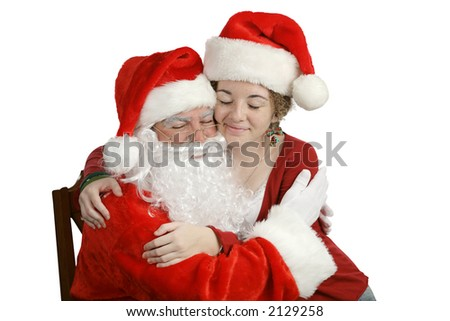 A girl sitting on Santa's lap and giving him a hug.  Isolated on white.