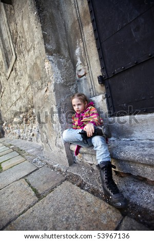 a girl sitting on steps on old wall background - stock photo