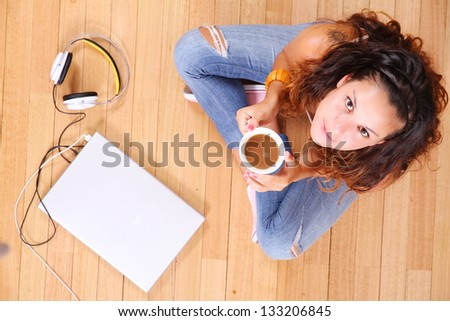 A girl sitting on the floor with a Laptop and some coffee. - stock photo