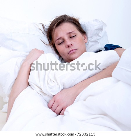 A girl sleeping in a bed with white sheets. - stock photo