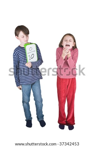 A girl sneezes into her hands, and a boy makes a thumbs down sign because this is one of the ways that swine flu is spread. He is holding a tablet on which is written a score of 0 out of 10. - stock photo