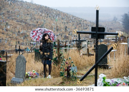 a girl standing at a cemetery under umbrella - stock photo