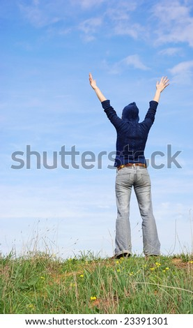 a girl standing on a hill with arms in the air - stock photo