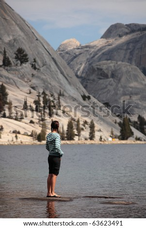 A girl stands at the shore of a lake in Yosemite national park.