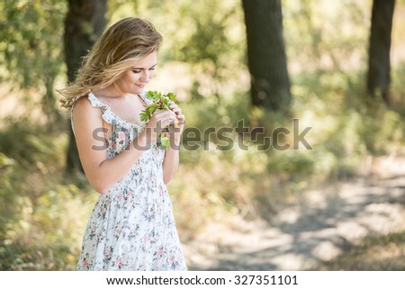 A girl stands in the oak alley with a branch in hand, looking at sprig. On a branch red berries. The wind blew her hair and dress the girl. Fain art film. - stock photo