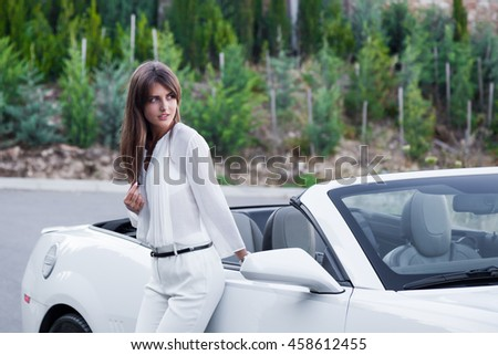 a girl stands near the white convertible