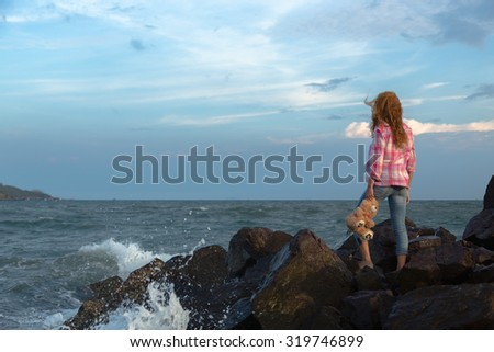A girl stands on the edge of a cliff holding a teddy bear. With a sense of hopelessness. - stock photo