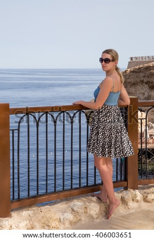 A girl stands on the terrace by the sea - stock photo