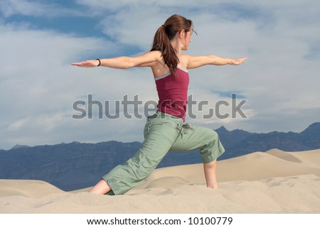 A girl strikes a yoga pose on a sand dune in Death Valley, California. - stock photo