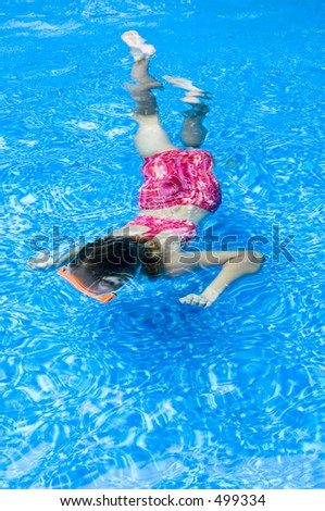 A girl swimming under water in a pool.