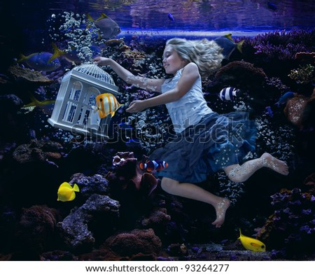 A girl swimming underwater  in a fish tank with a birdcage. - stock photo