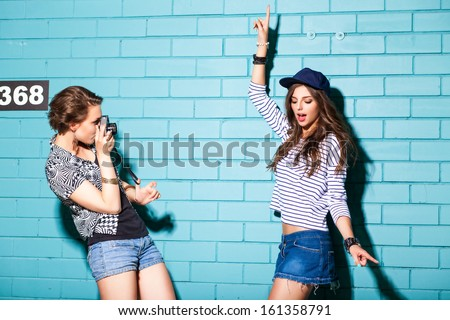 a girl takes picture of her friend in front of light blue brick wall - stock photo