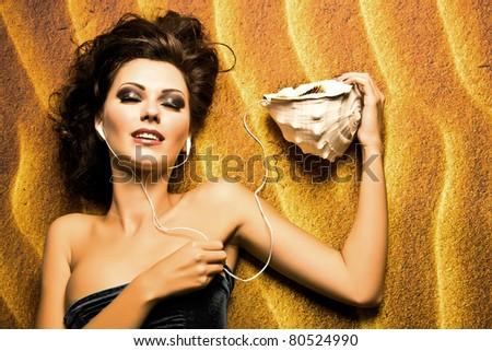 a girl taking a sunbath lying on the sand listening music - stock photo