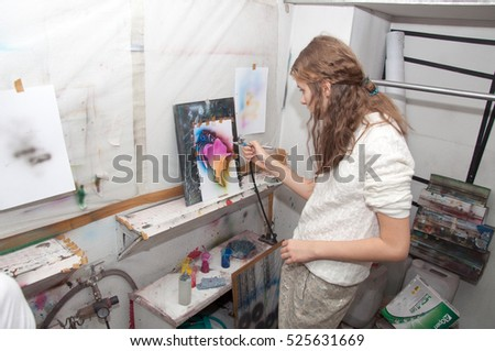 a girl teenager engaged in airbrushing paint brightly colored pictures in a artistical studio - Russia, Moscow - January 24, 2016