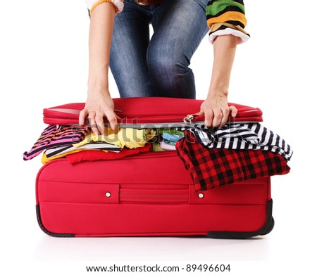 A girl tries to close the suitcase isolated on a white
