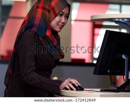 A girl using computer terminal in a library       - stock photo