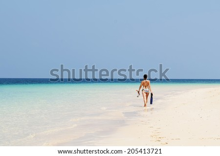 a girl walking at the beach with snorkeling gear