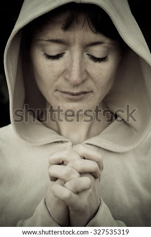 A girl wearing a jacket with a hood, put out his arms and folded her fingers together. As in prayer.