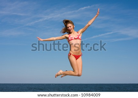 A girl wearing a red bikini having fun and jumping at the beach