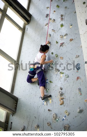 A girl wearing harness and belaying rope and climbing on a very high rock climbing wall. - stock photo