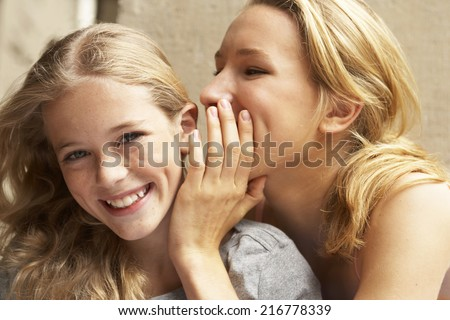 A girl whispering something into another girls ear. - stock photo