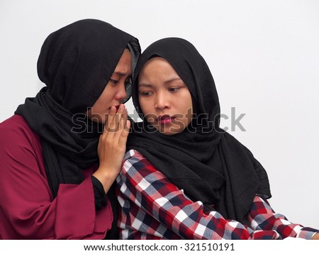 A girl whispering to a friend with white background.