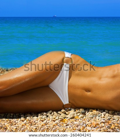 A girl with a beautiful slender figure against the sea - stock photo