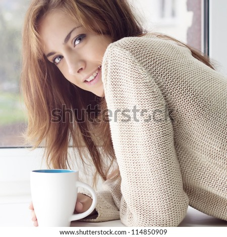 A girl with a charming smile and a glass on a window - stock photo