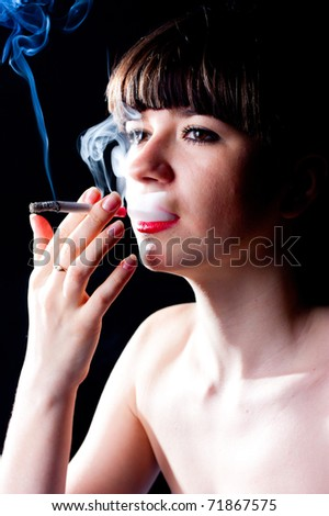 A girl with a cigarette on a black background - stock photo