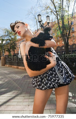 A girl with a dog standing on the street - stock photo