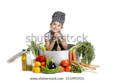 a girl with a huge cooking pot surrounded by vegetables - stock photo