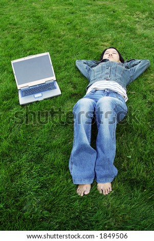A girl with a laptop taking a nap outdoor in a park
