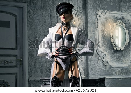 A girl with a perfect waist, in white lingerie and cap standing in a long coat - stock photo