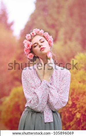 A girl with a wreath of roses, portrait series of girls in nature - stock photo