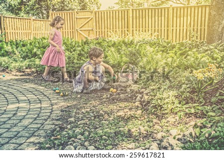 A girl with an Easter Basket collects colorful eggs as her sister comes to join the fun outside during an egg hunt.  Part of a series.  Filtered for a retro, vintage look. - stock photo