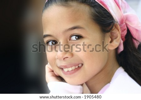 A girl with brown eyes and pink bandanna enjoying the outdoor. - stock photo