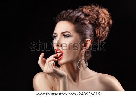 A girl with curly hair and coral lips showing tongue. - stock photo